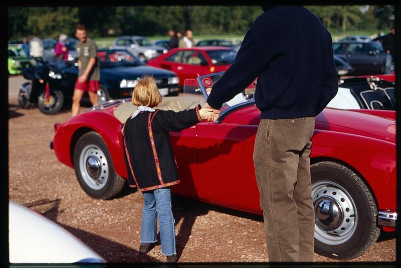 Une petite fille et son papa en visite à une expo de voitures