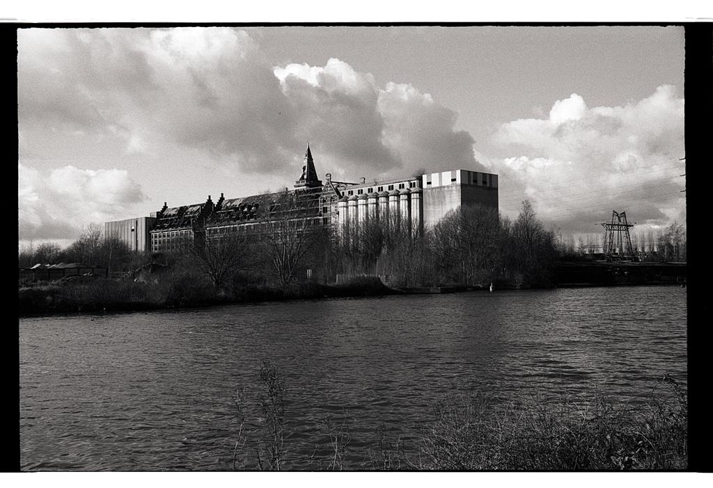 Kodak Tmax en 35 mm ancienne bâtisse des Moulins de Paris vue sur le canal de la Deûle près de Marquette photographie noir et blanc rétro sur pellicule Kodak. Photographe argentique Lille