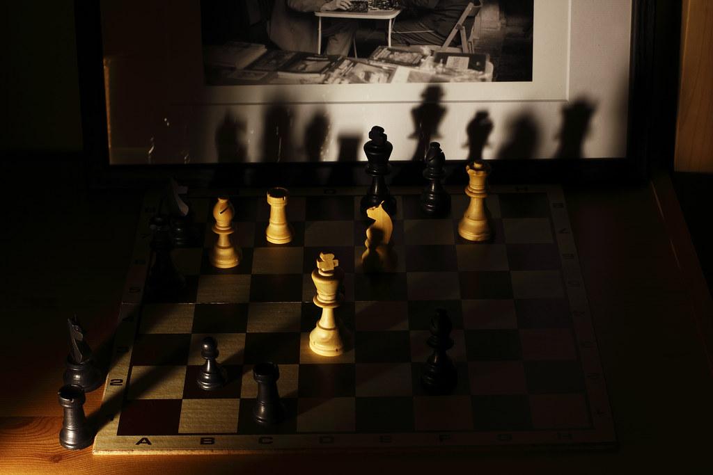 Jeu d'ombres et de lumière sur un plateau de jeu d'échecs.